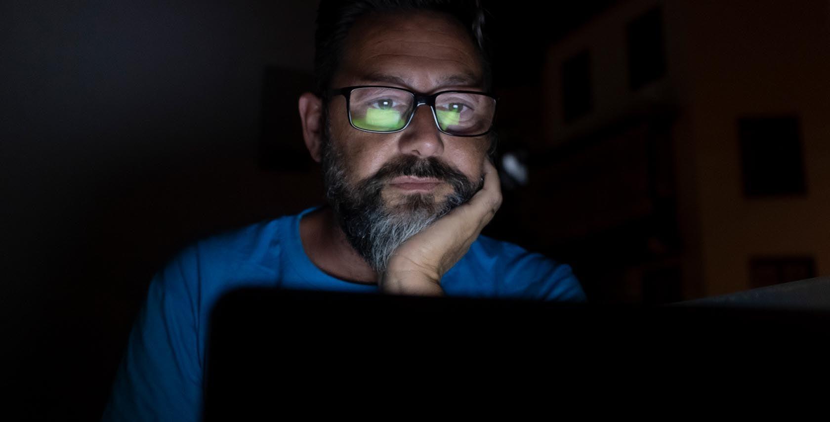 man staring at computer in the dark